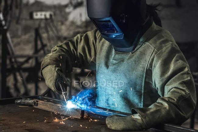 Trabajador manual en casco protector con antorcha de soldadura trabajando en taller - foto de stock