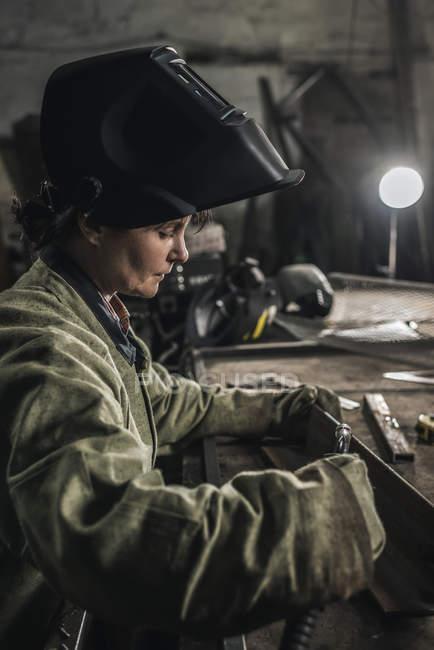 Fokussierte Handarbeiterin in Schutzkleidung in Werkstatt — Stockfoto