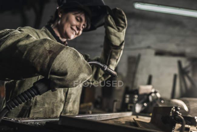 Selective focus of female welder in protective work wear working in workshop — Stock Photo
