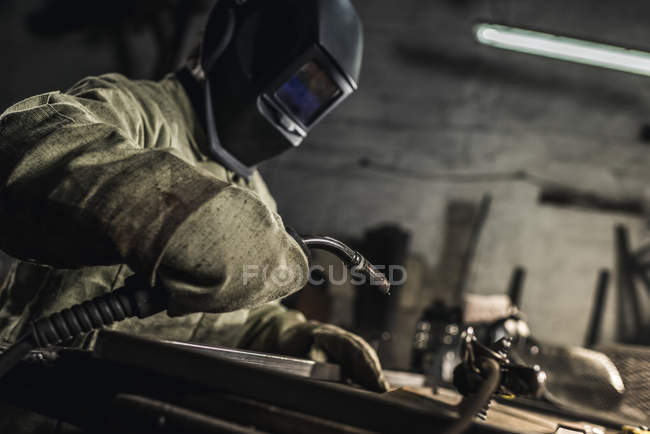 Side view of welder in protective work wear working with welding torch in workshop — Stock Photo