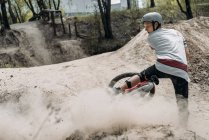 Poussière après coureur dans le casque vélo d'équitation — Photo de stock