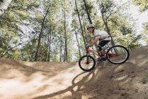 Езда на горном велосипеде по трассе в лесу — стоковое фото