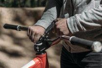 Geschnittenes Bild von Rennfahrer, der Fahrrad an der Natur befestigt — Stockfoto