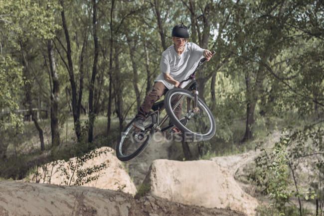 Piloto de salto com bicicleta de montanha na floresta — Fotografia de Stock