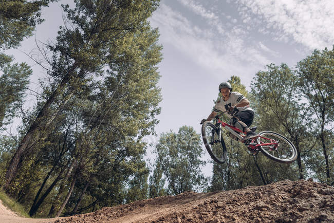Bottom view of sportsman jumping with bike — Stock Photo