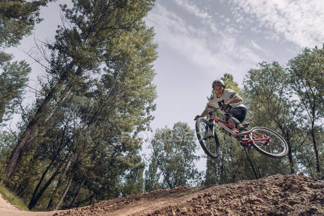 Vue de dessous du sportif sautant avec vélo — Photo de stock