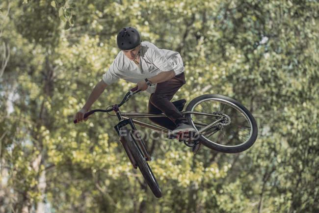 Спортсмен прыгает с велосипеда с деревьями на размытом фоне — стоковое фото