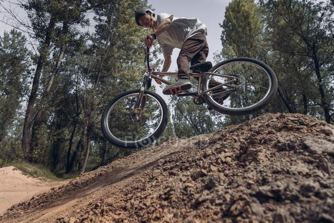 Вид снизу велосипедиста верхом на горном велосипеде по трассе в лесу — стоковое фото