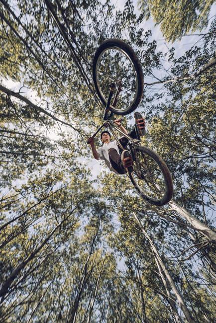 Vue de dessous du sportif saut à vélo entre les arbres — Photo de stock