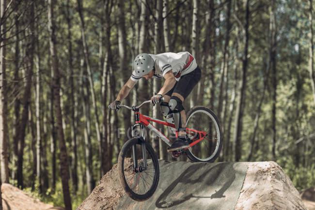 Гонщик велосипеда верхом на треке в лесу — стоковое фото