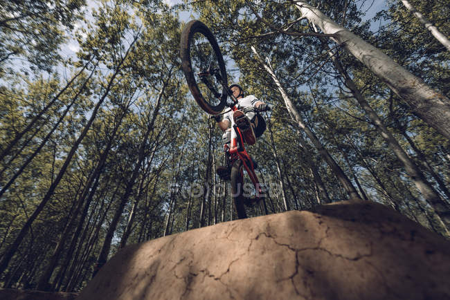 Bottom view of extreme sportsman jumping with mountain bike — Stock Photo