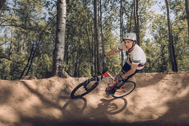 Cyclist riding mountain bike on track in forest — Stock Photo