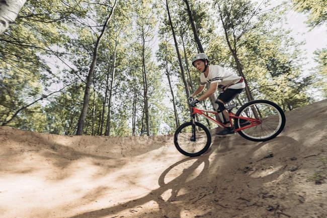 Гонщик езда велосипеде на треке в лесу — стоковое фото